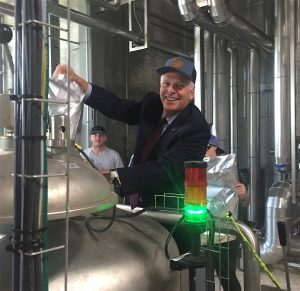 Virginia Gov. Terry McAuliffe dumps hops into the collaboration imperial stout brewed at Stone Brewing Co. in Richmond. Photo by Lee Graves
