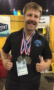 Ryan Aldridge, vice president of sales for Blue Mountain Brewery, sports the three medals won by the brewery's group. Photo by Lee Graves