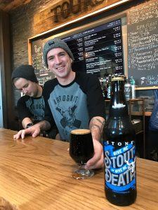Chase Dipple serves a glass of the collaborative imperial stout at Stone's tasting room. Photo by Lee Graves