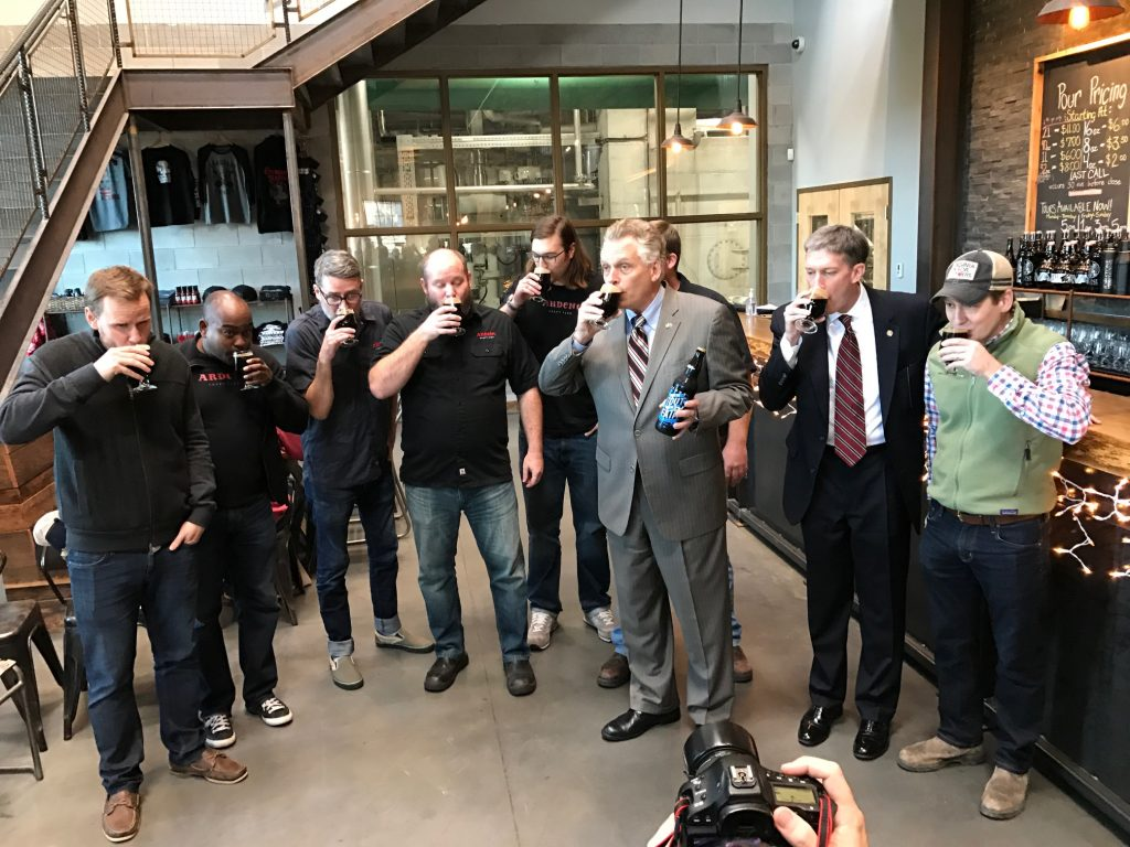 Gov. Terry McAuliffe (third from right in gray suit) and Todd Haymore (second from right), Secretary of Commerce and Trade, join representatives from Ardent Craft Ales and Hardywood Park Craft Brewery at Stone brewery in Richmond to celebrate the release of Give Me Stout or Give me Death. Photo by Lee Graves